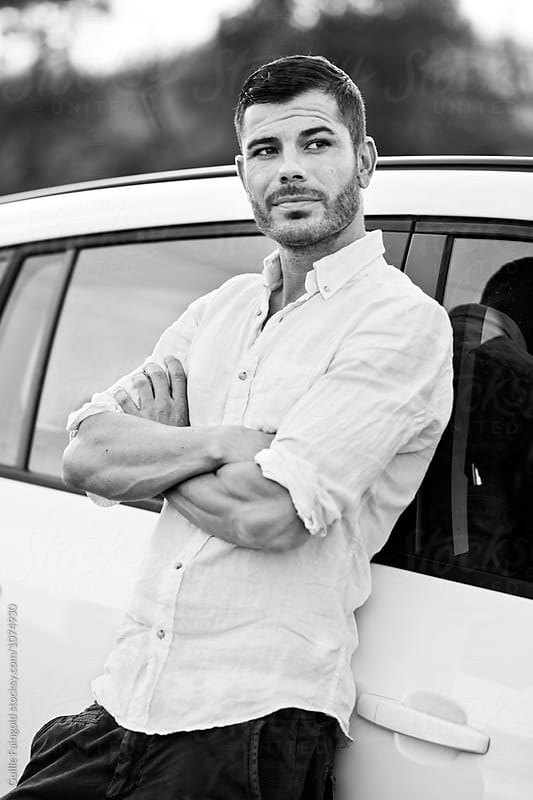 stylish bearded man with arms crossed leaning on car by Guille Faingold for Stocksy United