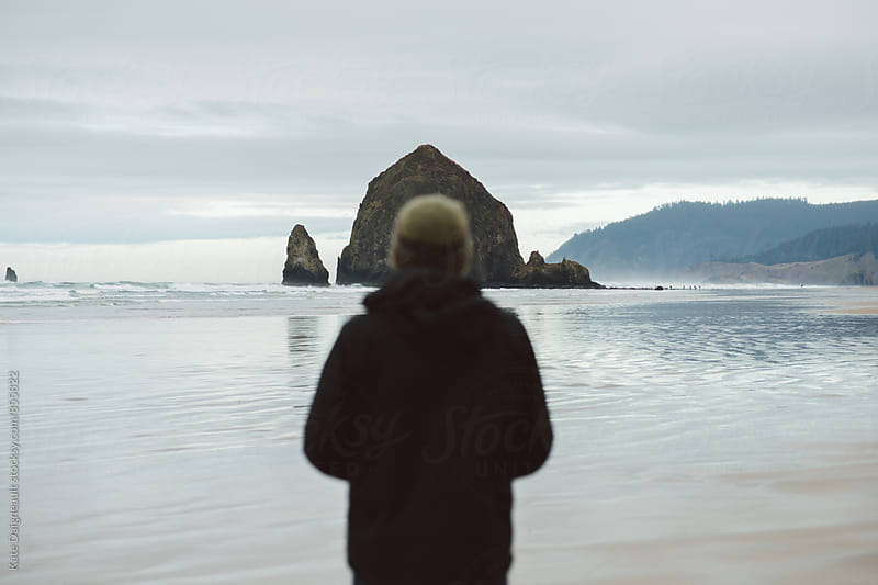 Young man standing looking at huge rock formation on the Oregon coast. by Kate Daigneault for Stocksy United