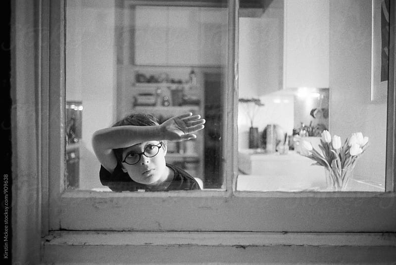 Boy looking out of a window at night. by Kirstin Mckee for Stocksy United