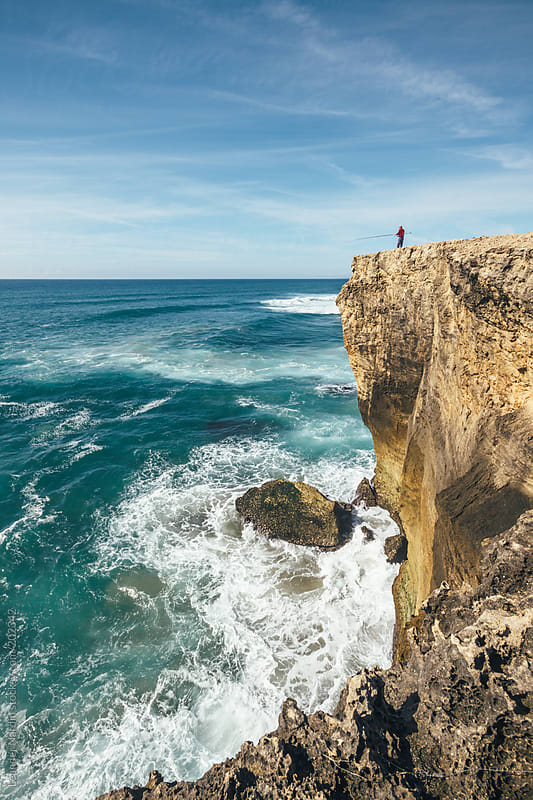 fisherman fishing on a big cliff  by Leander Nardin for Stocksy United