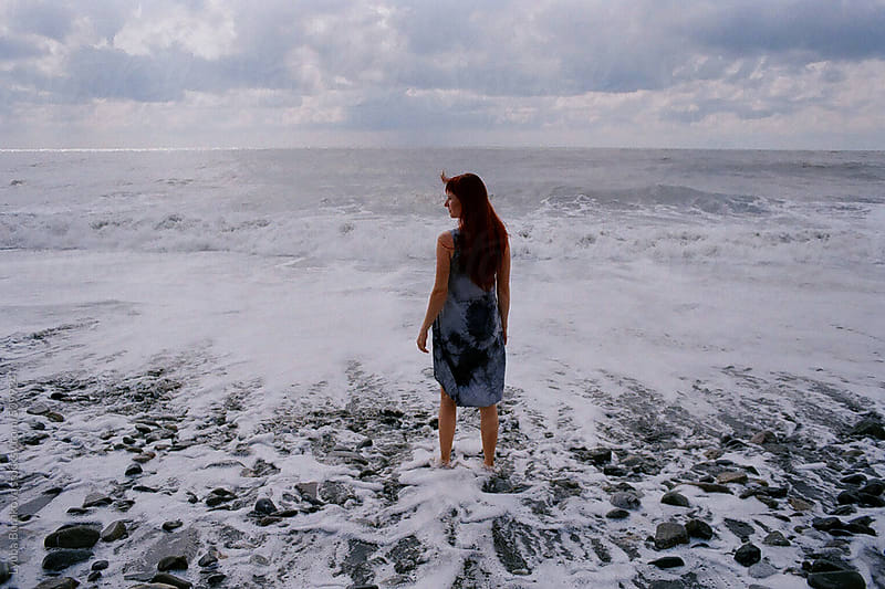 Back view of the woman standing in the white sea foam by Lyuba Burakova for Stocksy United
