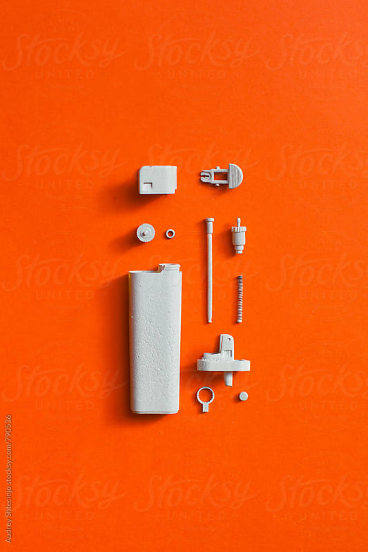 White disassembled lighter on orange/red background by Marko Milanovic for Stocksy United
