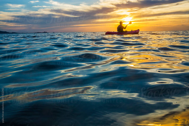 Kayaker at sunset in ocean by yuko hirao for Stocksy United