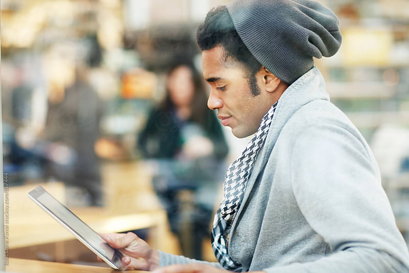 Man using a tablet in coffee shop by Isaac Lane Koval for Stocksy United