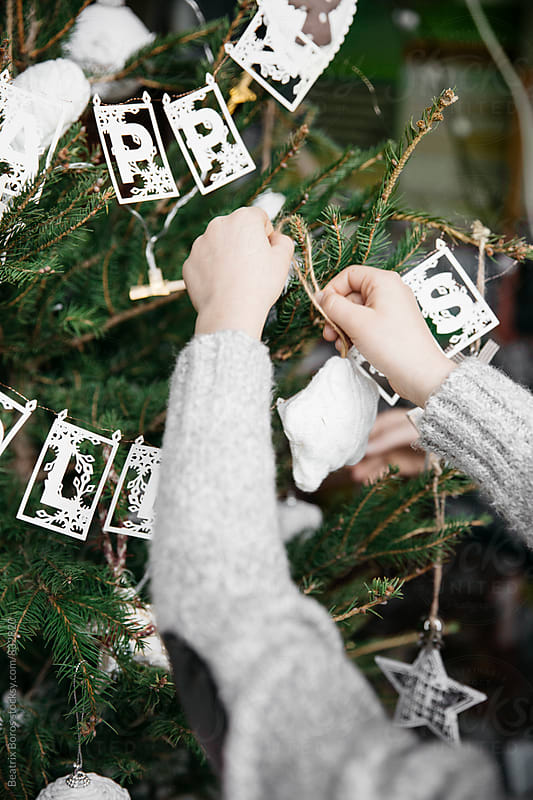 Hands decorating a Christmas tree by Beatrix Boros for Stocksy United