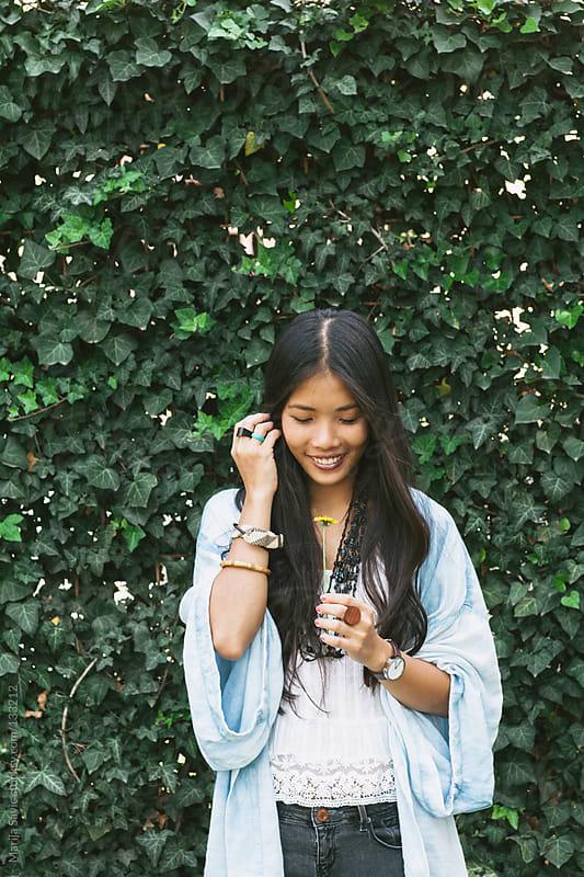 Beautiful Asian woman holding wildflower. by Marija Savic for Stocksy United