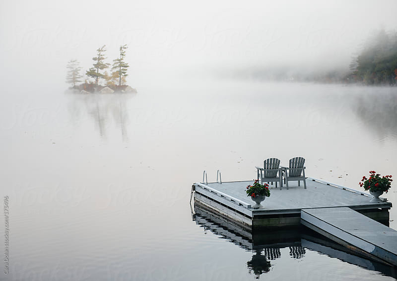 Dock floats on a lake with morning fog by Cara Dolan for Stocksy United