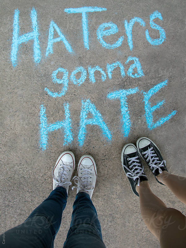 Two kids standing above chalk words that say Haters gonna Hate by Carolyn Lagattuta for Stocksy United