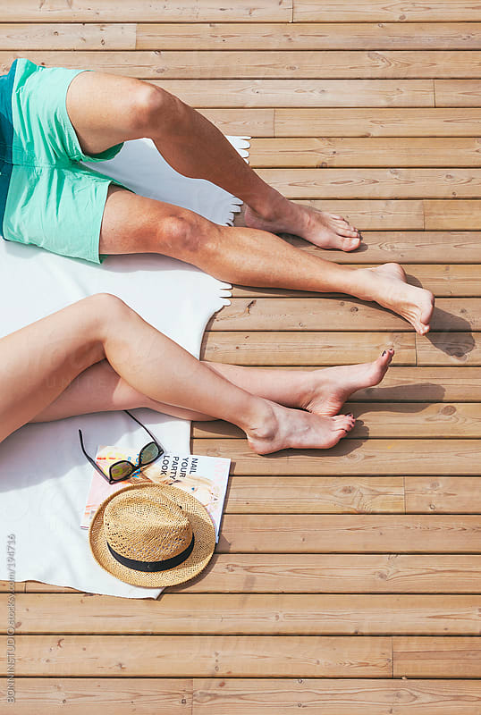 Cropped view of beautiful couple sunbathing on a wooden terrace. Summer time. by BONNINSTUDIO for Stocksy United