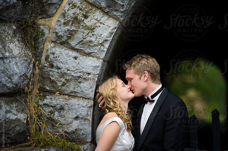 Handsome Classic Couple Kisses By Stone Railroad Tunnel by Brian McEntire for Stocksy United