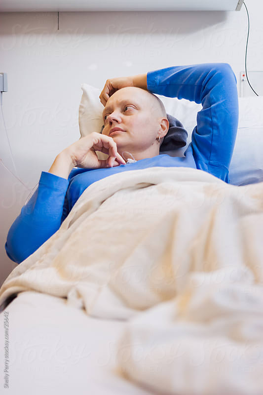 Woman at the hospital for a round of chemotherapy, cancer treatment by Shelly Perry for Stocksy United