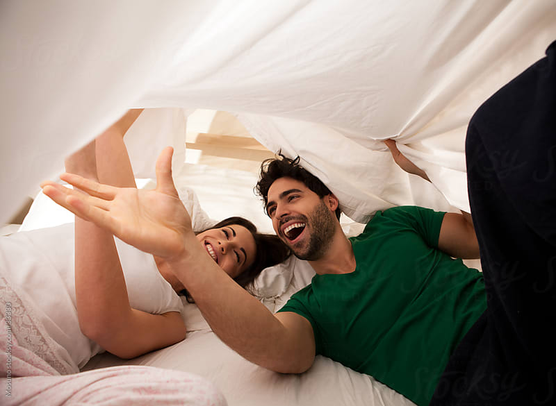 Young carefree couple laughing and enjoying morning in bed.  by Mosuno for Stocksy United