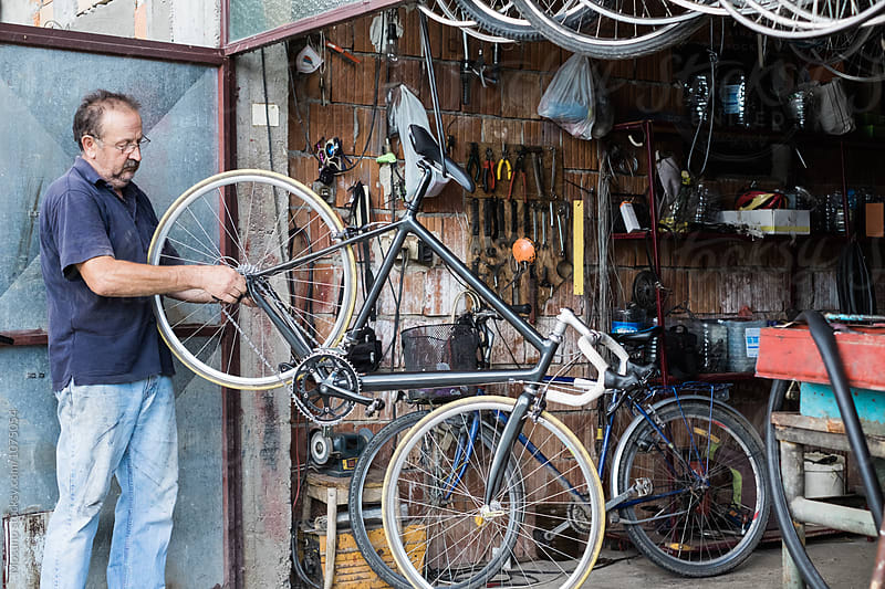 Man Repairs a Bike in a Garage by Mosuno for Stocksy United