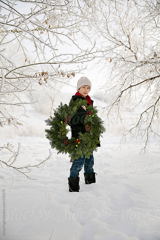 Boy with winter wreath by Dana Pugh for Stocksy United