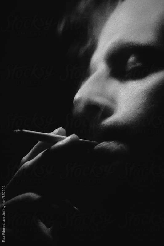 Close up of man smoking cigarette by Paul Edmondson for Stocksy United