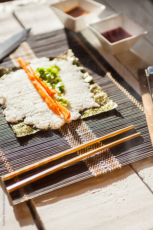 Chopsticks for eating sushi on dinner table. by Audrey Shtecinjo for Stocksy United