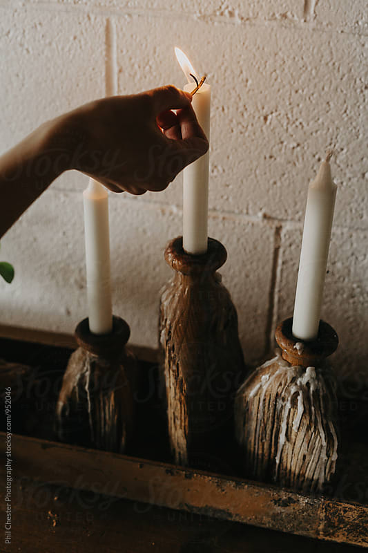 Hand lighting white candles in apartment with matches by Phil Chester Photography for Stocksy United