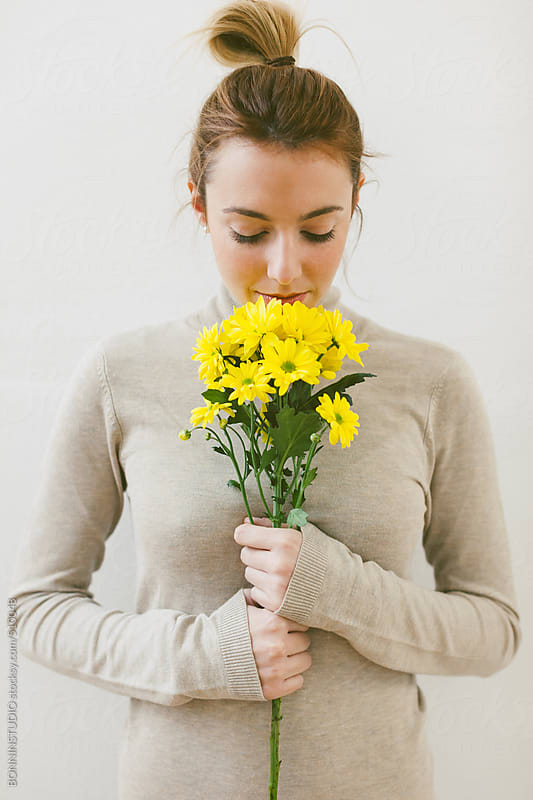 Portrait of young woman smelling a bouquet of yellow flowers.  by BONNINSTUDIO for Stocksy United
