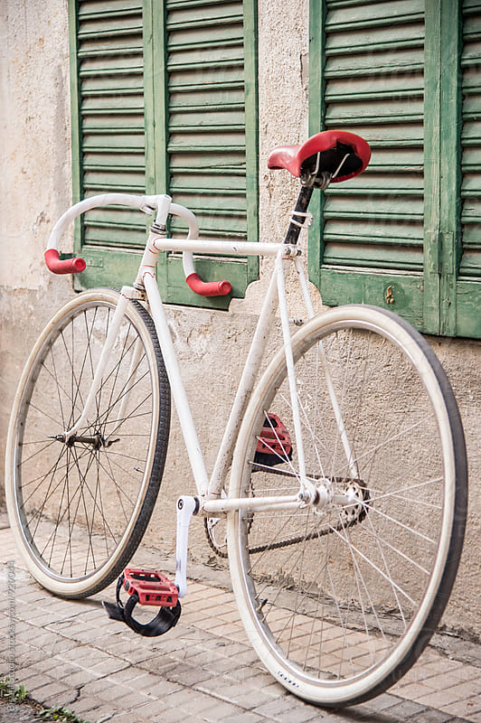 White vintage bicycle with a red saddle by Bisual Studio for Stocksy United