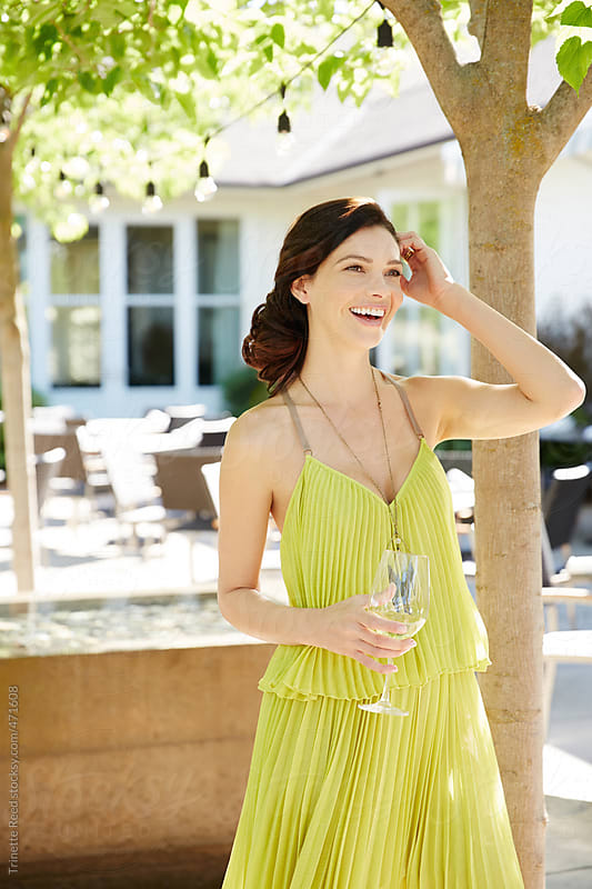 Beautiful woman with wine glass at outdoor restaurant and lounge by Trinette Reed for Stocksy United