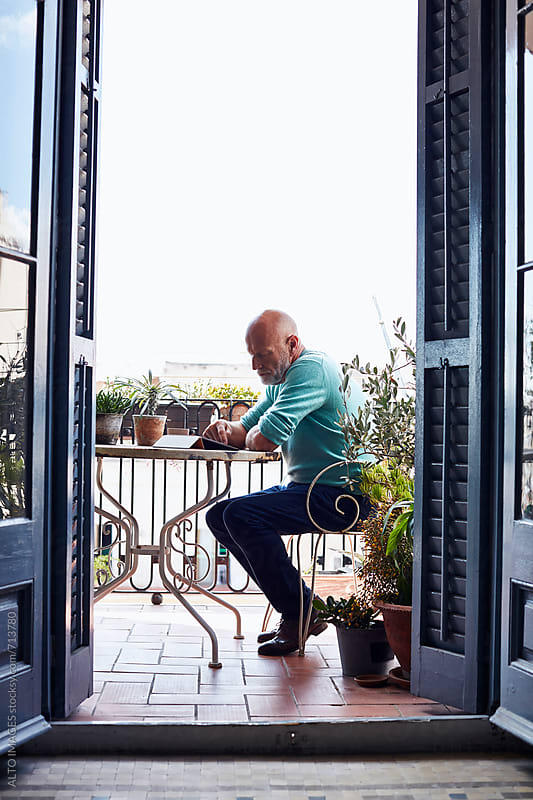Senior Man Using Digital Tablet On Balcony by ALTO IMAGES for Stocksy United