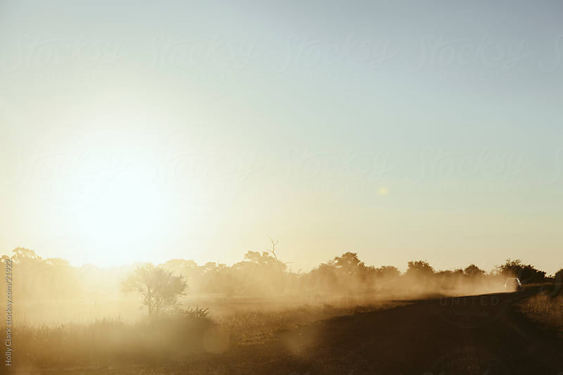 Car Drives Down Dusty Road by Holly Clark for Stocksy United