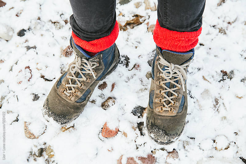 POV shot of Woman's feet with hiking boots and red socks in the snow by Lior + Lone for Stocksy United