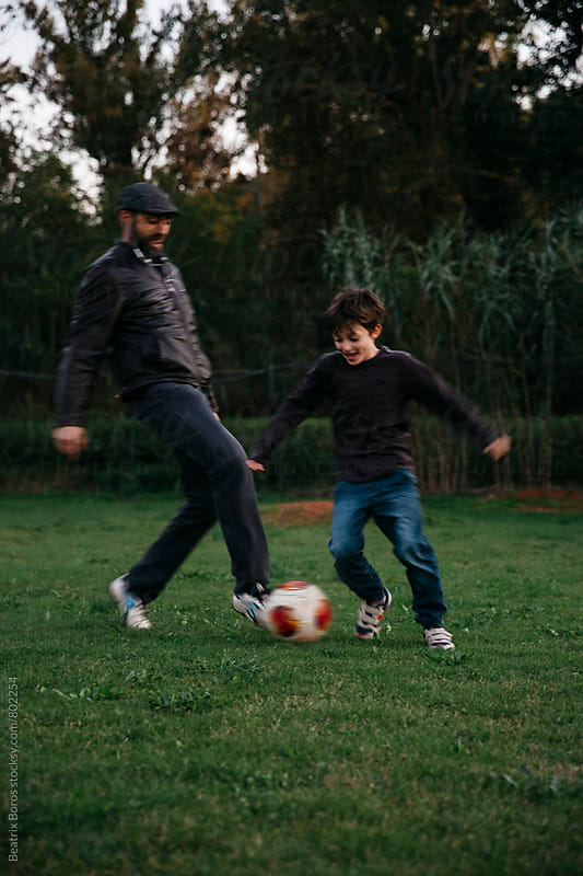 Man playing soccer with his son by Beatrix Boros for Stocksy United