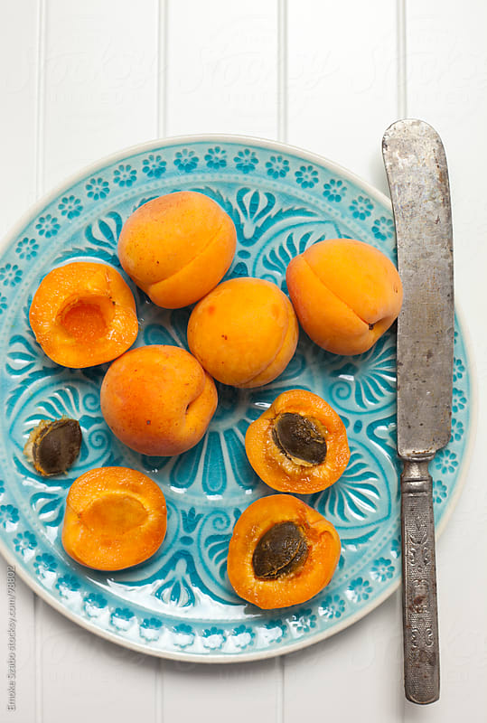 Apricots on a blue plate by Emoke Szabo for Stocksy United