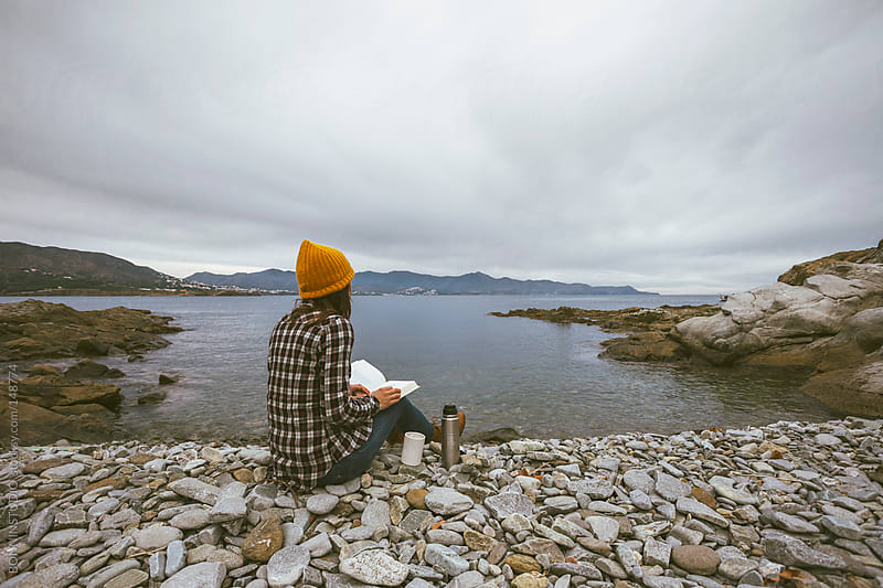 Young woman reading a book. She is sitting at seashore. by BONNINSTUDIO for Stocksy United