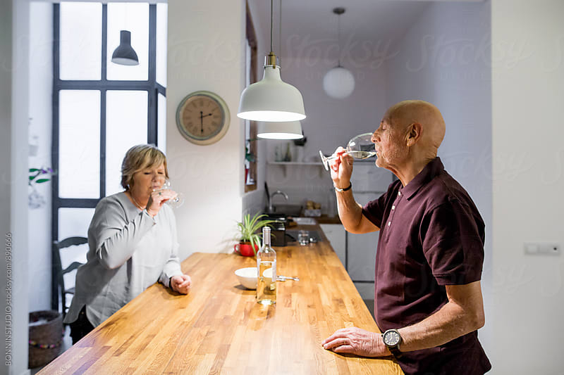 Elderly couple drinking wine in the kitchen. by BONNINSTUDIO for Stocksy United