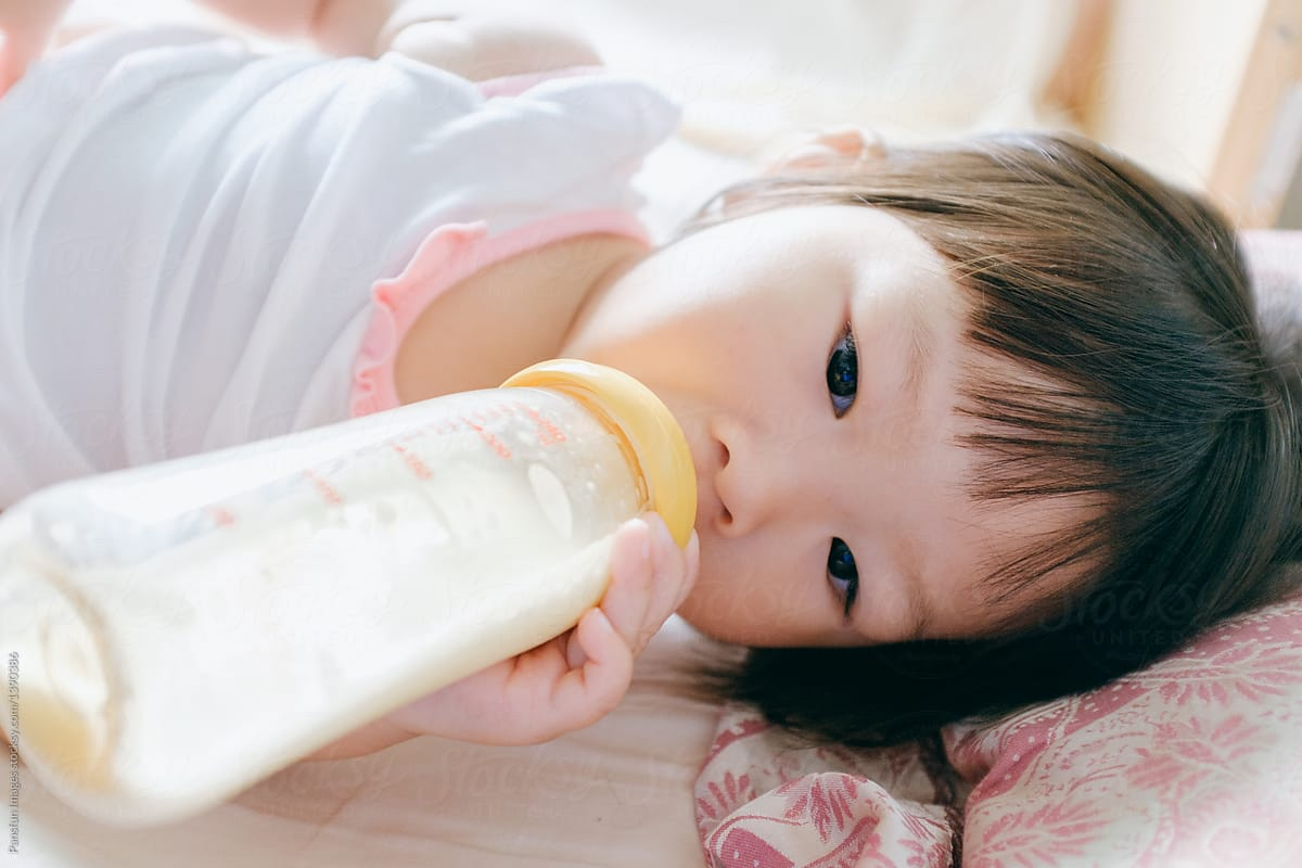 Asian Little Girl With A Bottle Of Milk by Pansfun Images - Asian, Milk