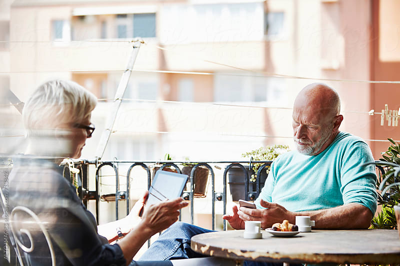 Senior Couple Using Technologies On Balcony by ALTO IMAGES for Stocksy United