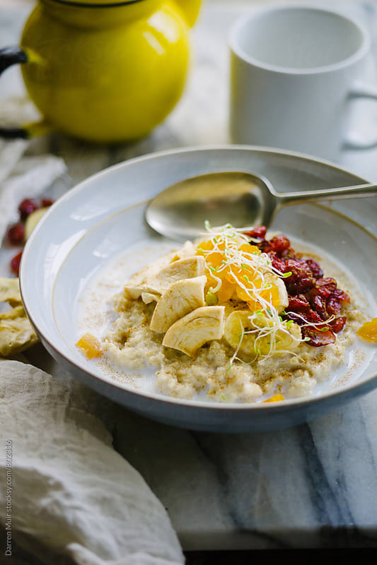 Breakfast: Healthy bowl of oat porridge with dried fruits. by Darren Muir for Stocksy United