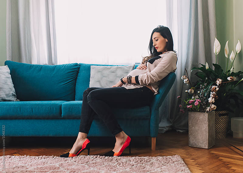 Pregnant Woman Sitting  on a Couch by Lumina for Stocksy United