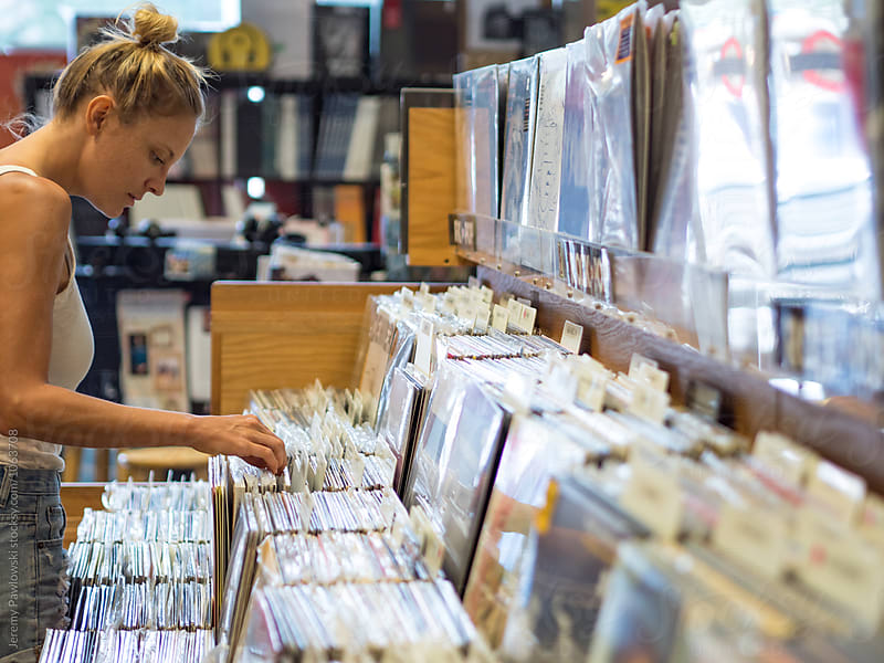 Young hipster woman thumbing through vinyl records by Jeremy Pawlowski for Stocksy United
