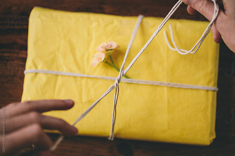 Hands tying a knot wrapping a gift by Lior + Lone for Stocksy United