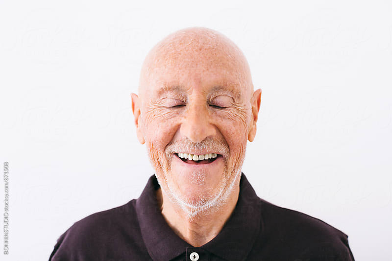 Portrait of an elderly man laughing with eyes closed over white. by BONNINSTUDIO for Stocksy United