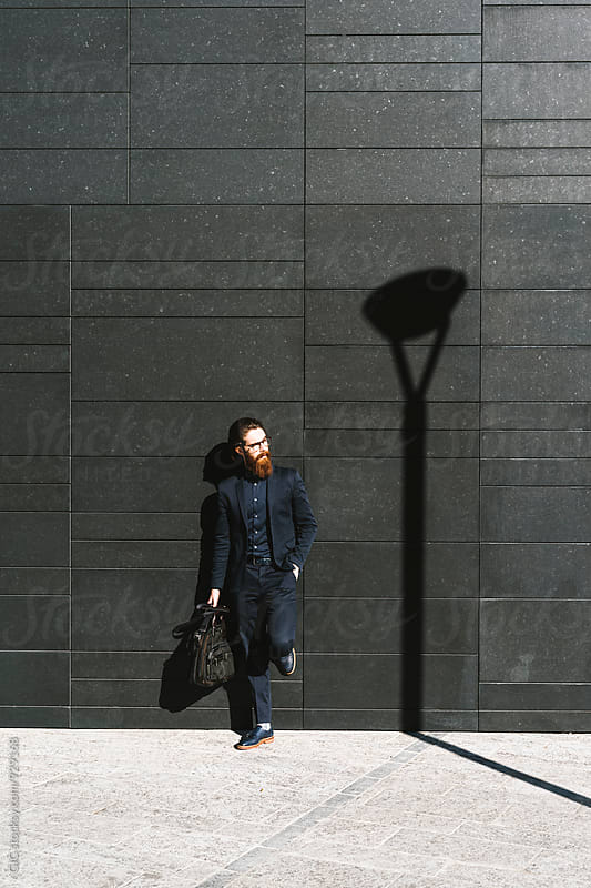 Trendy businessman standing against a black wall in the city by Simone Becchetti for Stocksy United