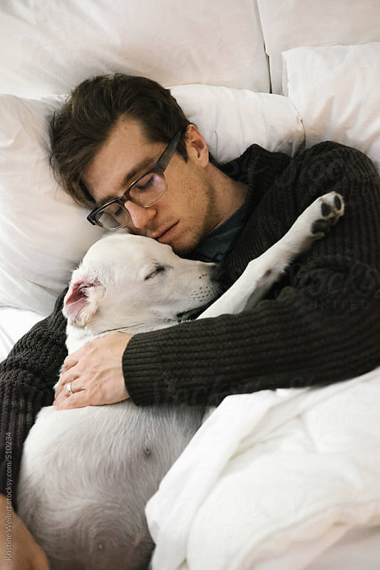 Man sleeping with puppy in his arms by Kristine Weilert for Stocksy United