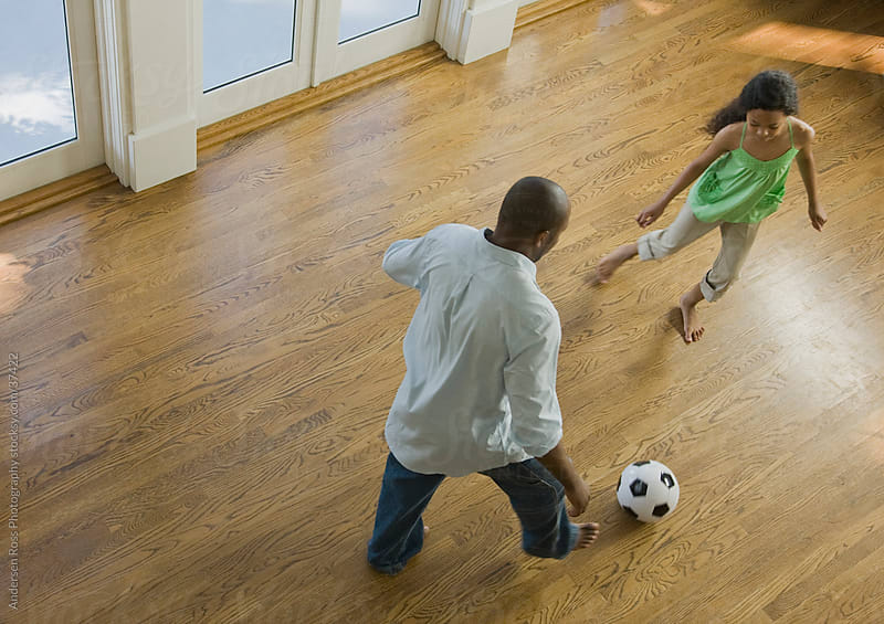 Man with daughter (12-13) playing soccer at home by Andersen Ross Photography for Stocksy United