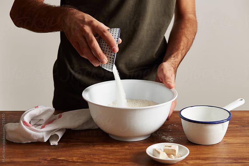 Preparing cinnamon rolls by Martí Sans for Stocksy United