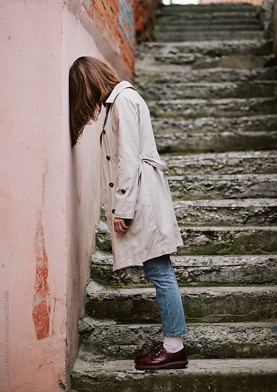 A young girl stands against the wall by Sergey Filimonov for Stocksy United