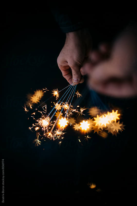 Man's both hands holding sparklers in the dark, the closer ones making handmade bokeh star shapes by Beatrix Boros for Stocksy United