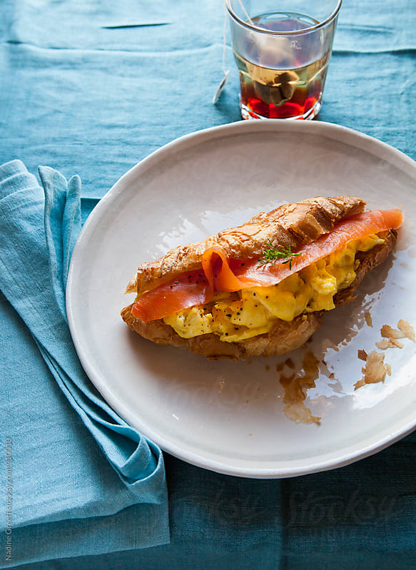Scrambled eggs with smoked salmon on croissant by Nadine Greeff for Stocksy United