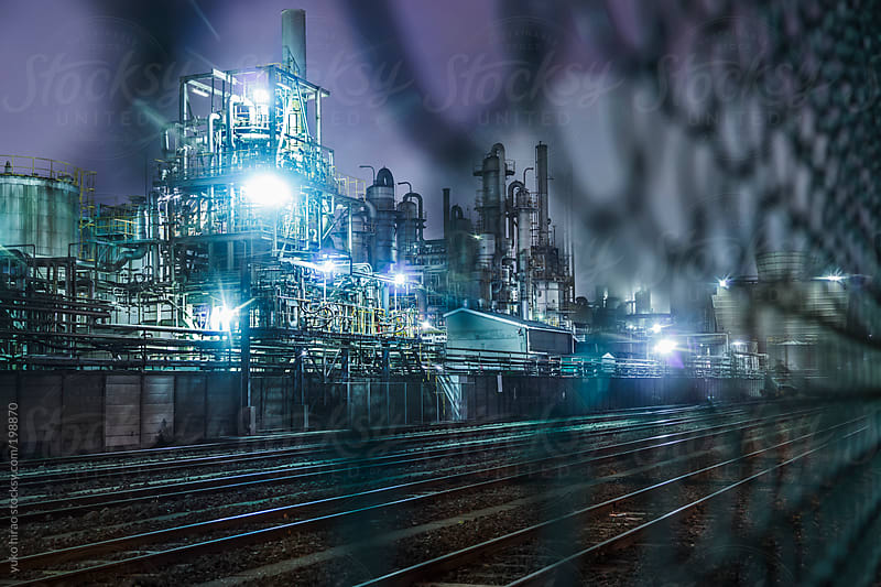 Chemical factories and railroad behind fence at night by yuko hirao for Stocksy United
