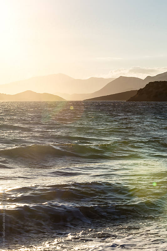 Mountains beyond Waves at Sea at Sunset by Helen Sotiriadis for Stocksy United
