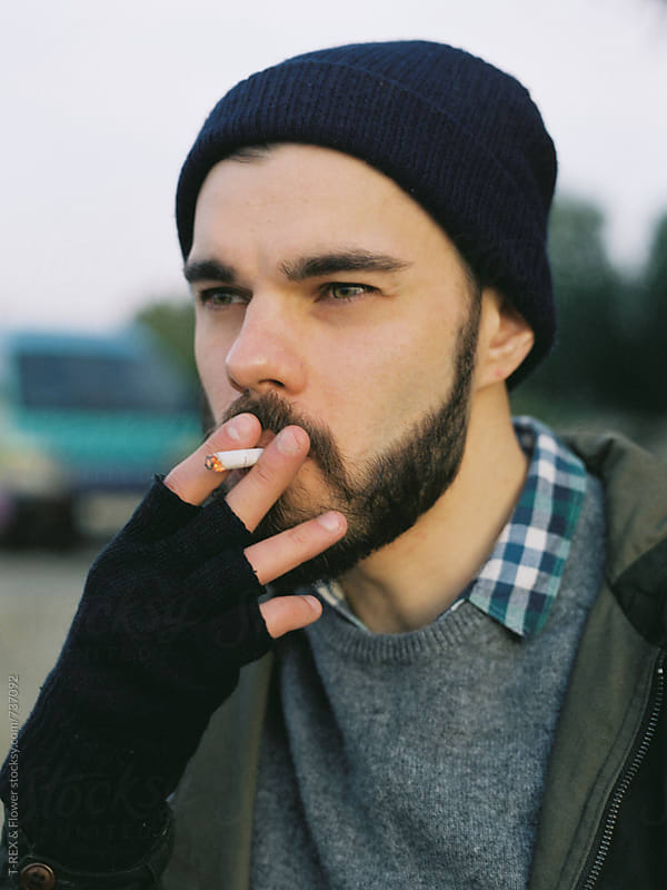 Portrait of a man smoking cigarette by Danil Nevsky for Stocksy United