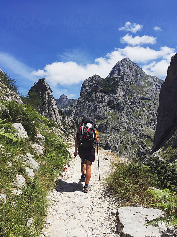 Female hiker walking on the Senda del Cares trail  by Luca Pierro for Stocksy United