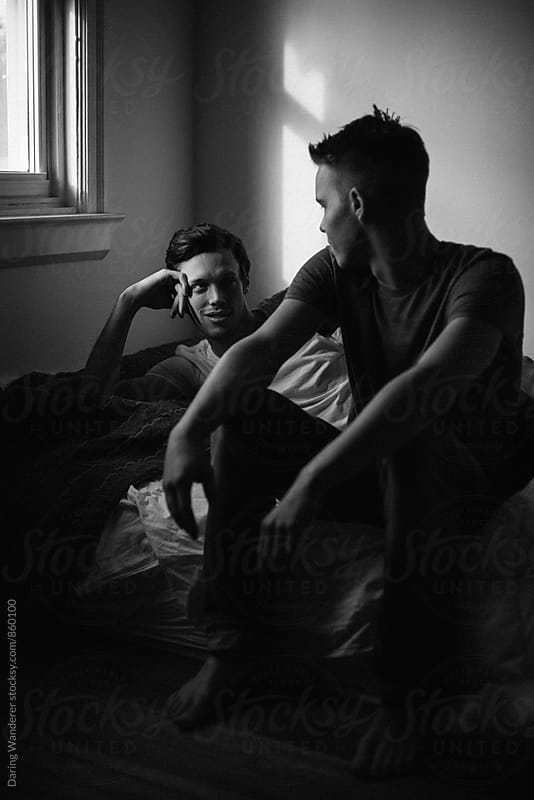 Young attractive gay couple waking up in bed in the morning by Daring Wanderer for Stocksy United
